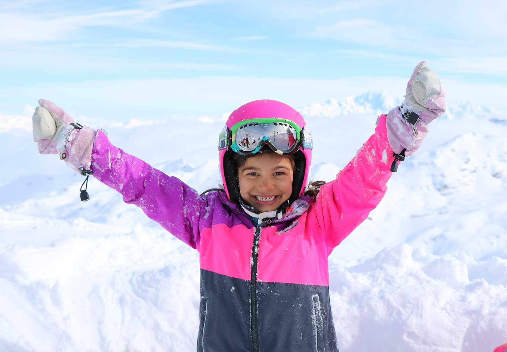 enfant qui sourit pendant un cours de ski